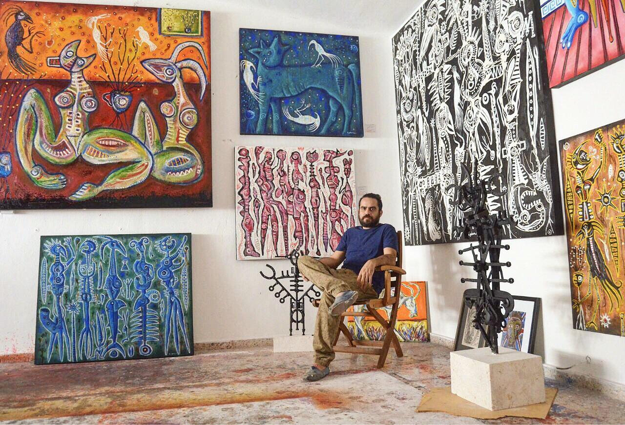 El joven artista plástico Carlos Génova con algunas de sus obras.